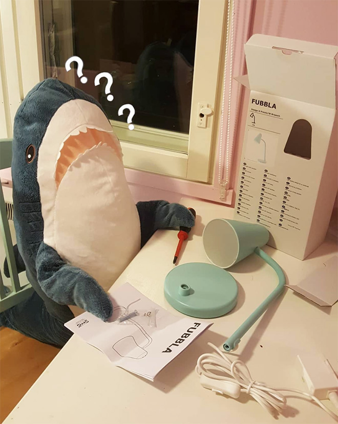 IKEA shark putting together IKEA lamp.