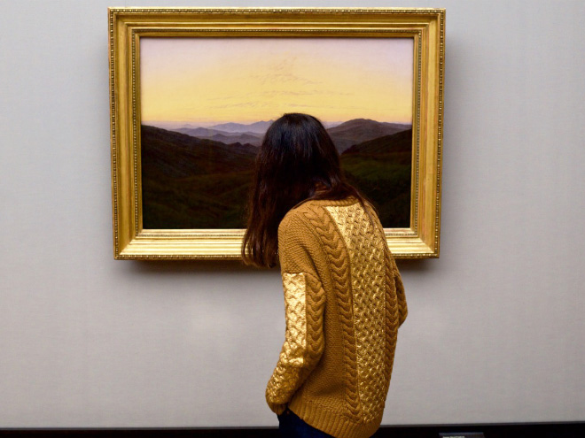 Painting's frame perfectly matching museum visitor's sweater.