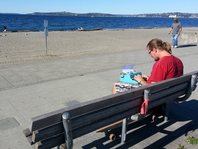 Hipster writing poetry at the beach.