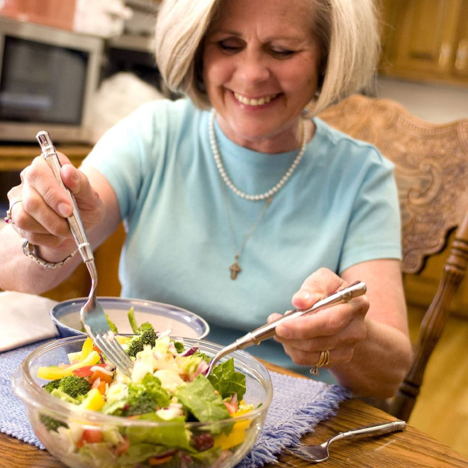 Woman laughing alone with salad.