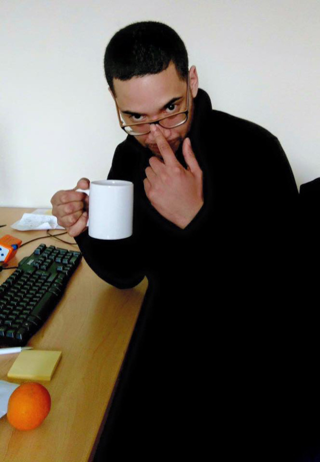 Handsome black man drinking coffee or tea.