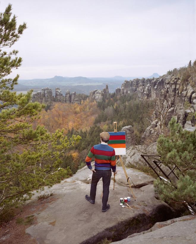 Artist visiting sceninc landscape to paint his own shirt.