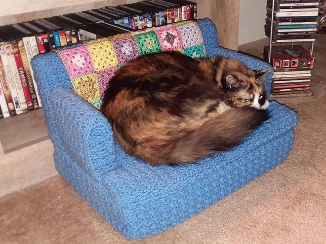 Cat on a tiny crocheted sofa.